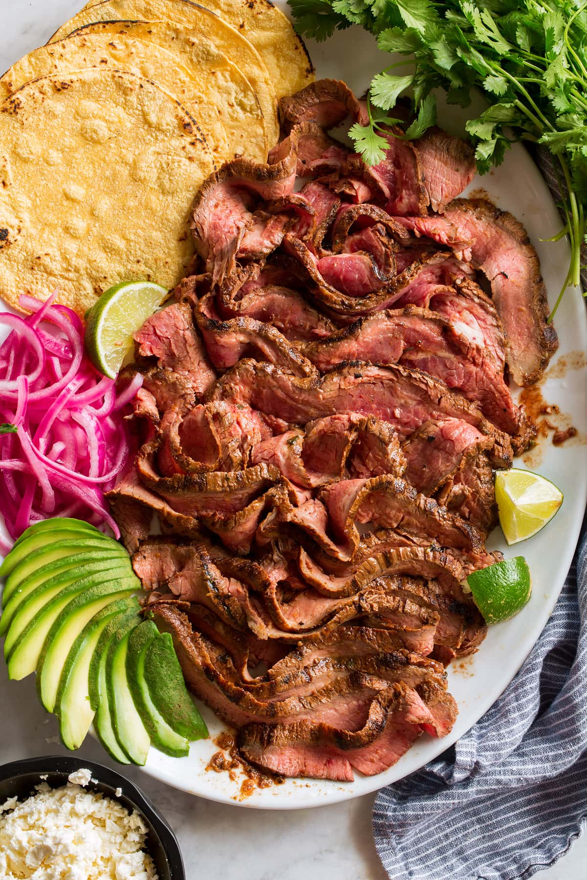 Overhead image of thin sliced carne asada on a serving platter with tortillas, onions, avocado, lime and cilantro.