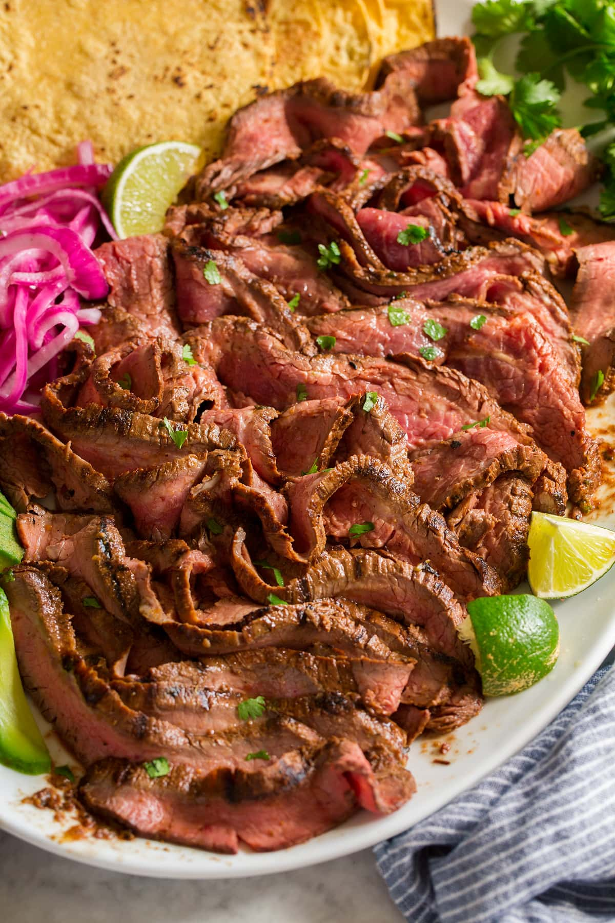 Sliced strips of carne asada shown on a white platter from a side view.