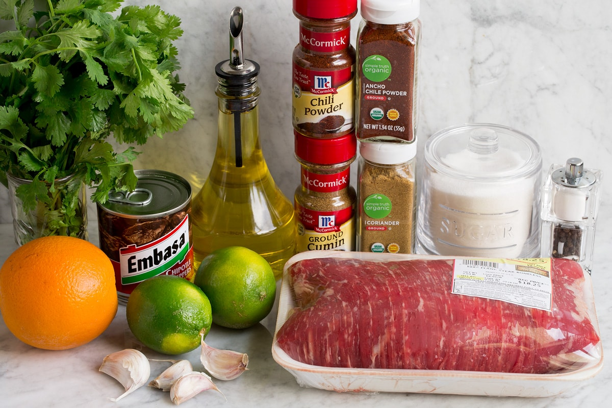 Image of ingredients used to make carne asada and marinade. Includes flank steak, cilantro, olive oil, chili powders, cumin, chipotle peppers, limes, oranges, sugar, garlic, salt and pepper.