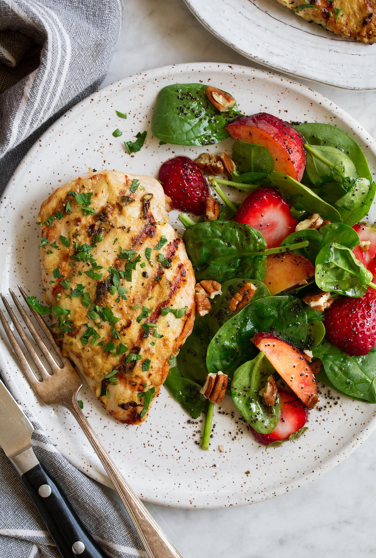 Dijon chicken shown on a serving plate with a side of spinach strawberry salad and poppy seed dressing.