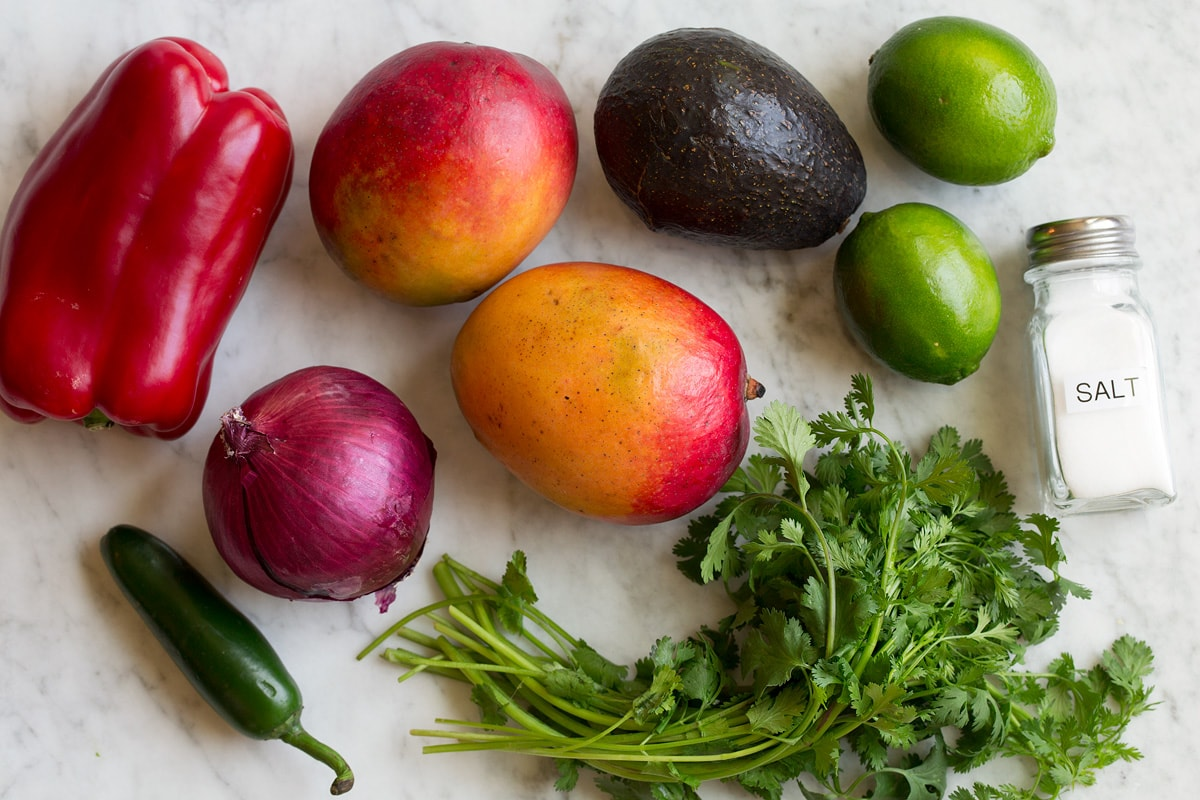 Image of ingredients used in mango salsa. Includes fresh mangoes, avocado, bell pepper, cilantro, red onion, lime, jalapeno and salt.