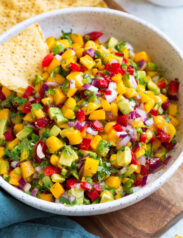Bowl of mango salsa with a side of tortilla chips.