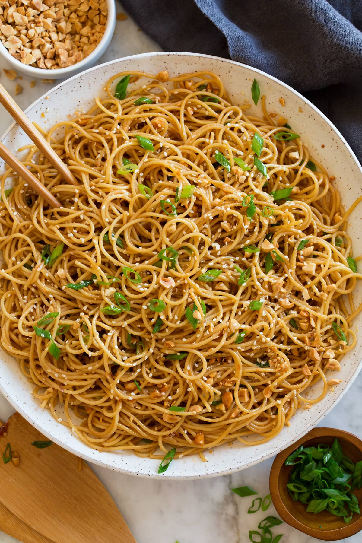 Photo: Bowl of sesame noodles topped with peanuts, sliced green onions and sesame seeds. Shown overhead in a white bowl with a dark napkin underneath and chopsticks and serving spoons to the side.