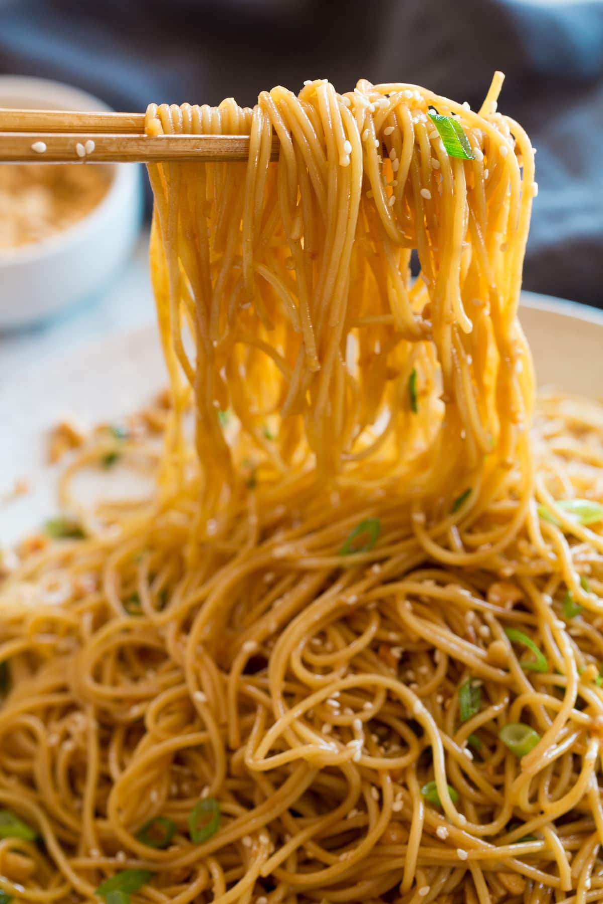 Photo: Sesame noodles shown close hanging over chopsticks.