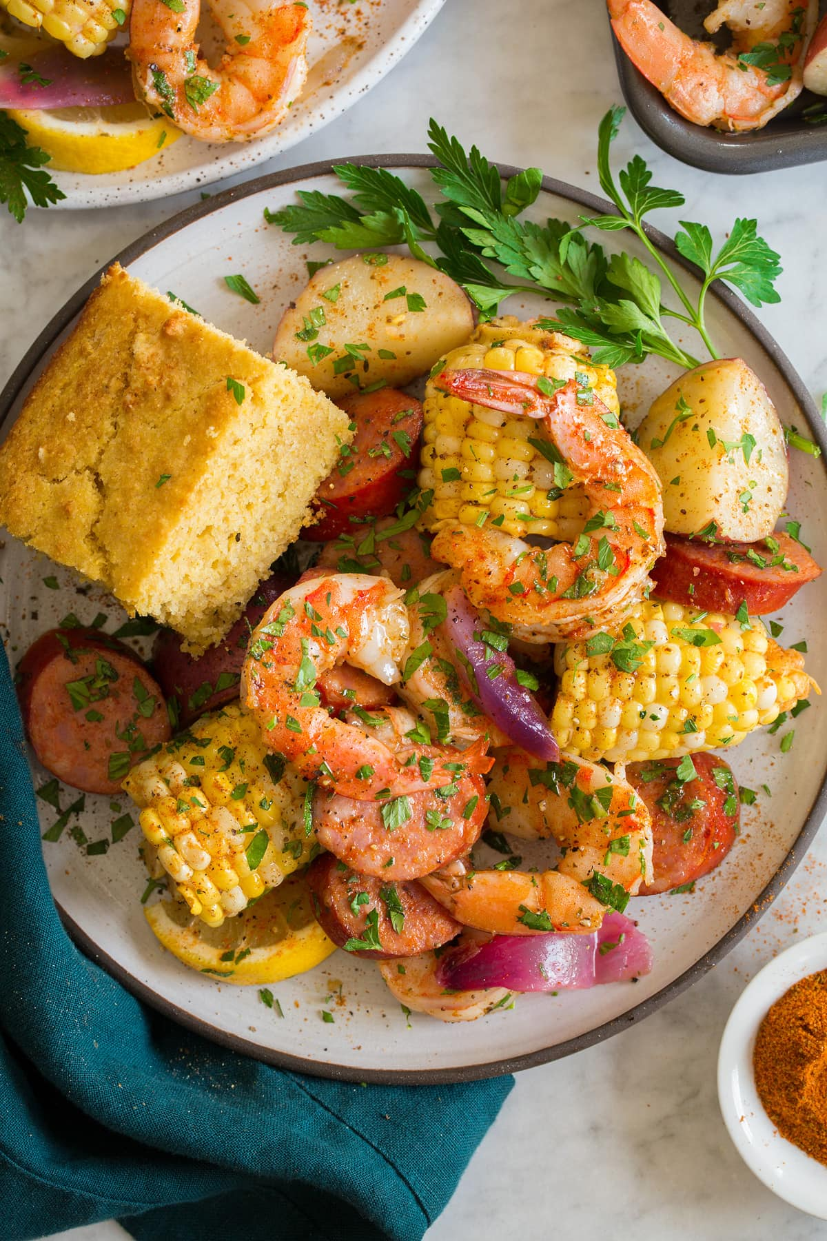 Image showing single serving of shrimp boil on a white plate with a serving suggestion of a side of cornbread.