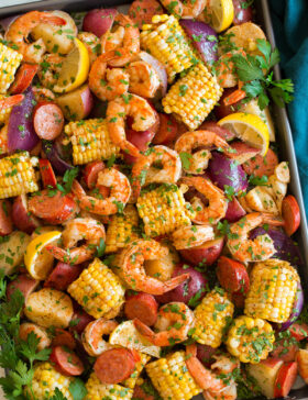 Image shown overhead of shrimp boil after cooking poured out and spread onto a large baking sheet.