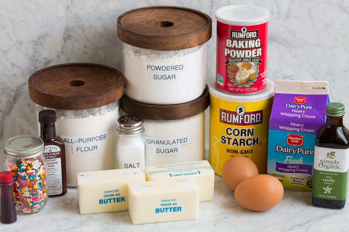 Image of ingredients that are used to make sugar cookie bars. Includes flour, sugar, powdered sugar, butter, eggs, baking powder, cornstarch, cream, vanilla, almond extract, sprinkles and food coloring.