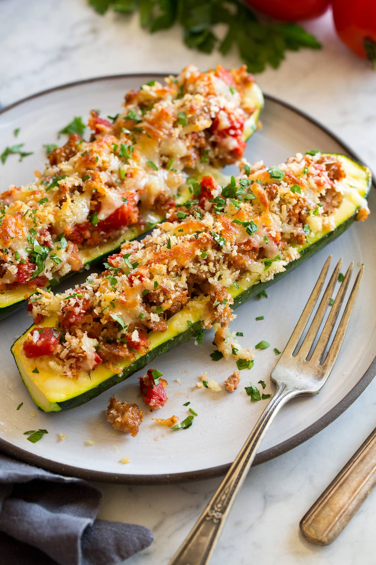 Two stuffed zucchini boats on a white dinner plate with a fork to the side.