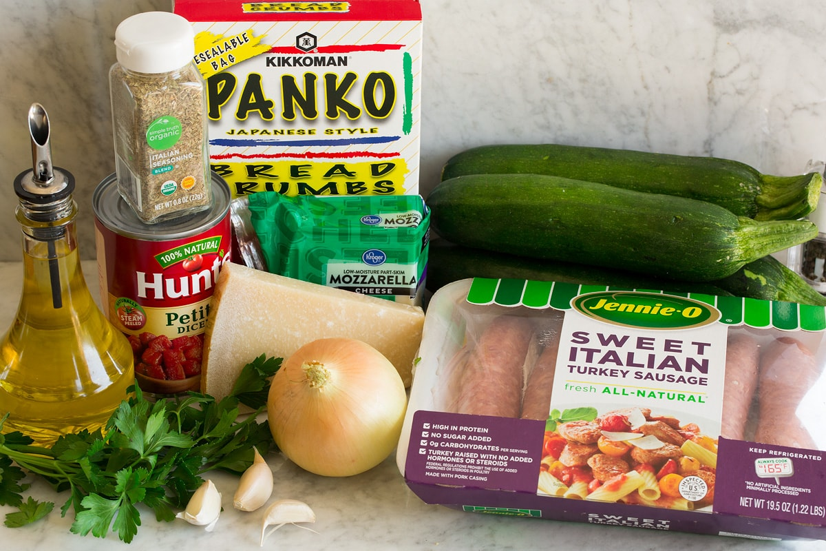 Image of ingredients used to make zucchini boats. Shows sausage, zucchini, onion, parmesan, parsley, garlic, mozzarella, tomatoes, Italian seasoning, panko bread crunbs and olive oil.