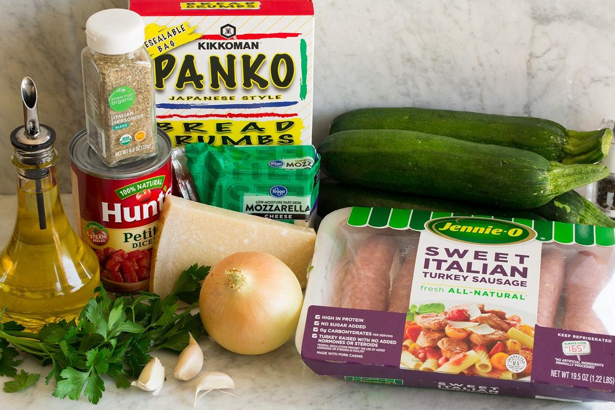 Image of ingredients used to make zucchini boats. Shows sausage, zucchini, onion, parmesan, parsley, garlic, mozzarella, tomatoes, Italian seasoning, panko bread crunbs and olive oil.