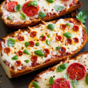 French Bread Pizza shown from a side angle on a baking sheet.