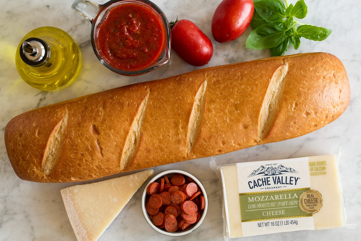 Image showing ingredients used to make French bread pizza. Includes French bread, cheeses, basil, pizza sauce, olive oil, pepperoni, tomatoes and basil.