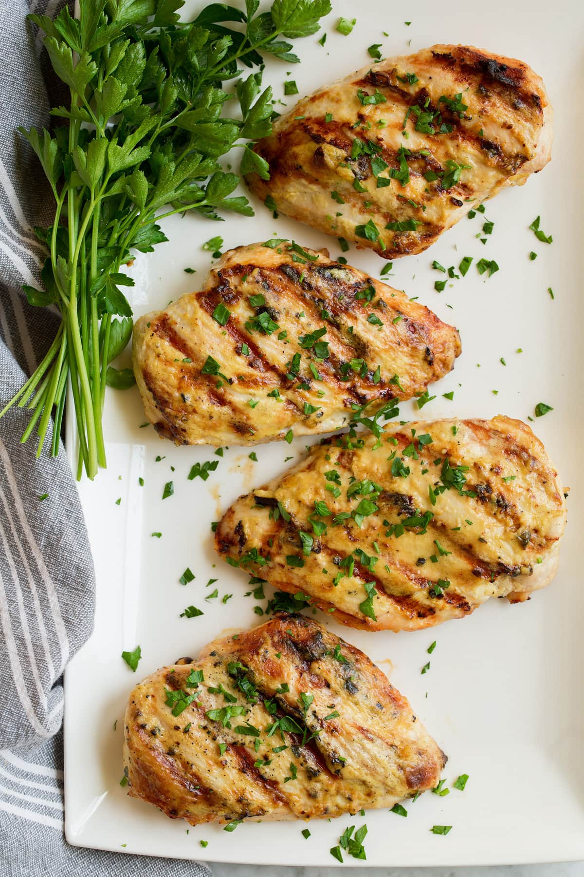 Overhead image of four chicken breasts that have been coated with a dijon mustard sauce and grilled. Chicken is resting on a rectangular white platter with a side of parsley.