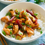 White bowl filled with rice and kung pao chicken.