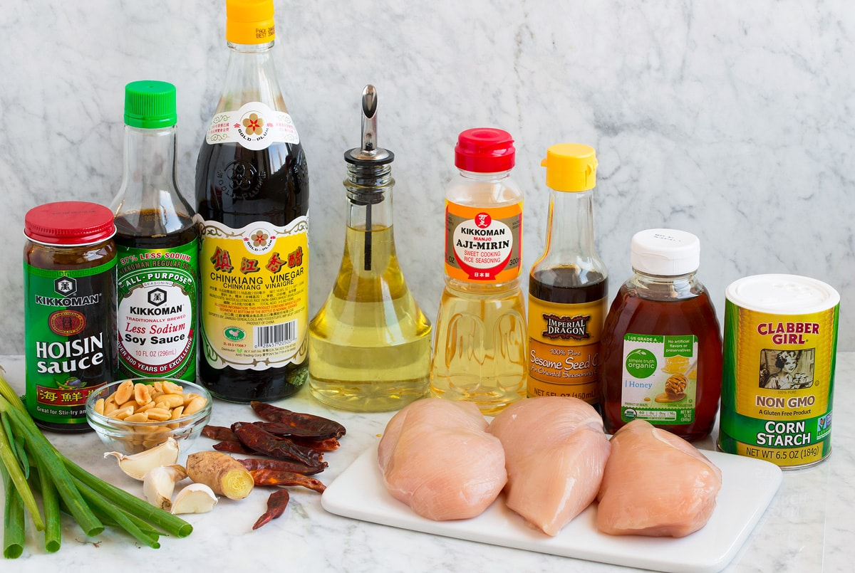 Image of ingredients used to make Kung Pao Chicken. Shows chicken, cornstarch, honey, sesame oil, mirin, vegetable oil, red chili peppers, garlic, ginger, soy sauce, peanuts, hoisin sauce, Chinese vinegar and green onions.