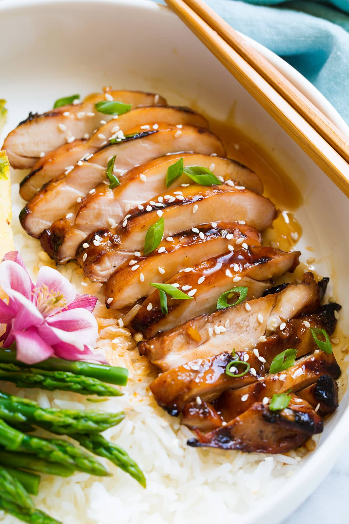 Sliced chicken thigh shown after cooking, covered in teriyaki sauce, sesame seeds and green onions.
