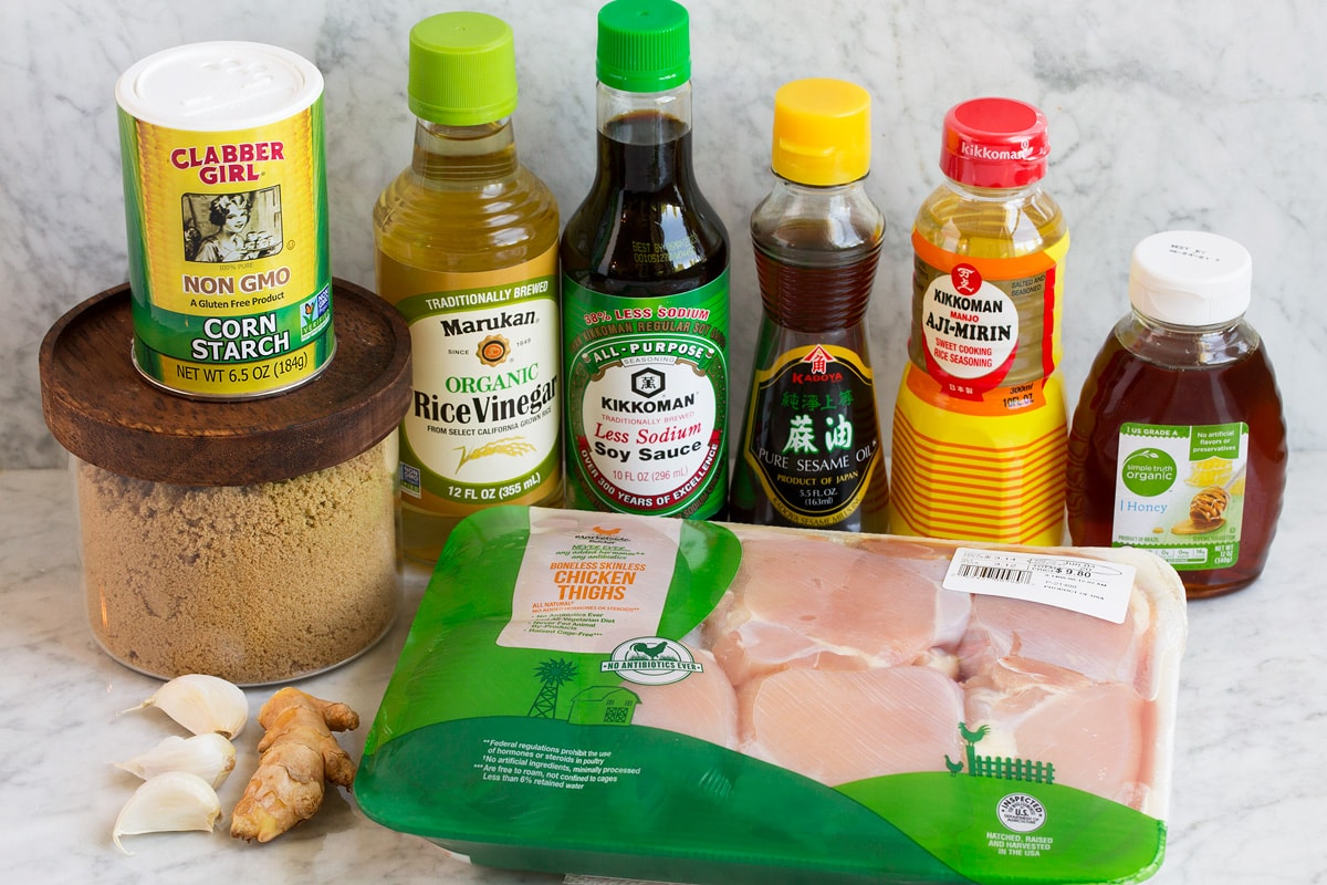 Image of ingredients used to make teriyaki chicken marinade. Includes soy sauce, rice vinegar, mirin, sesame oil, brown sugar, honey, ginger, garlic, chicken thighs and cornstarch.