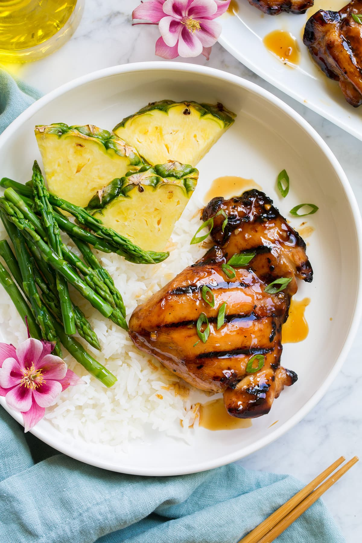 Piece of marinated and grilled teriyaki chicken shown served with rice, asparagus and fresh pineapple.