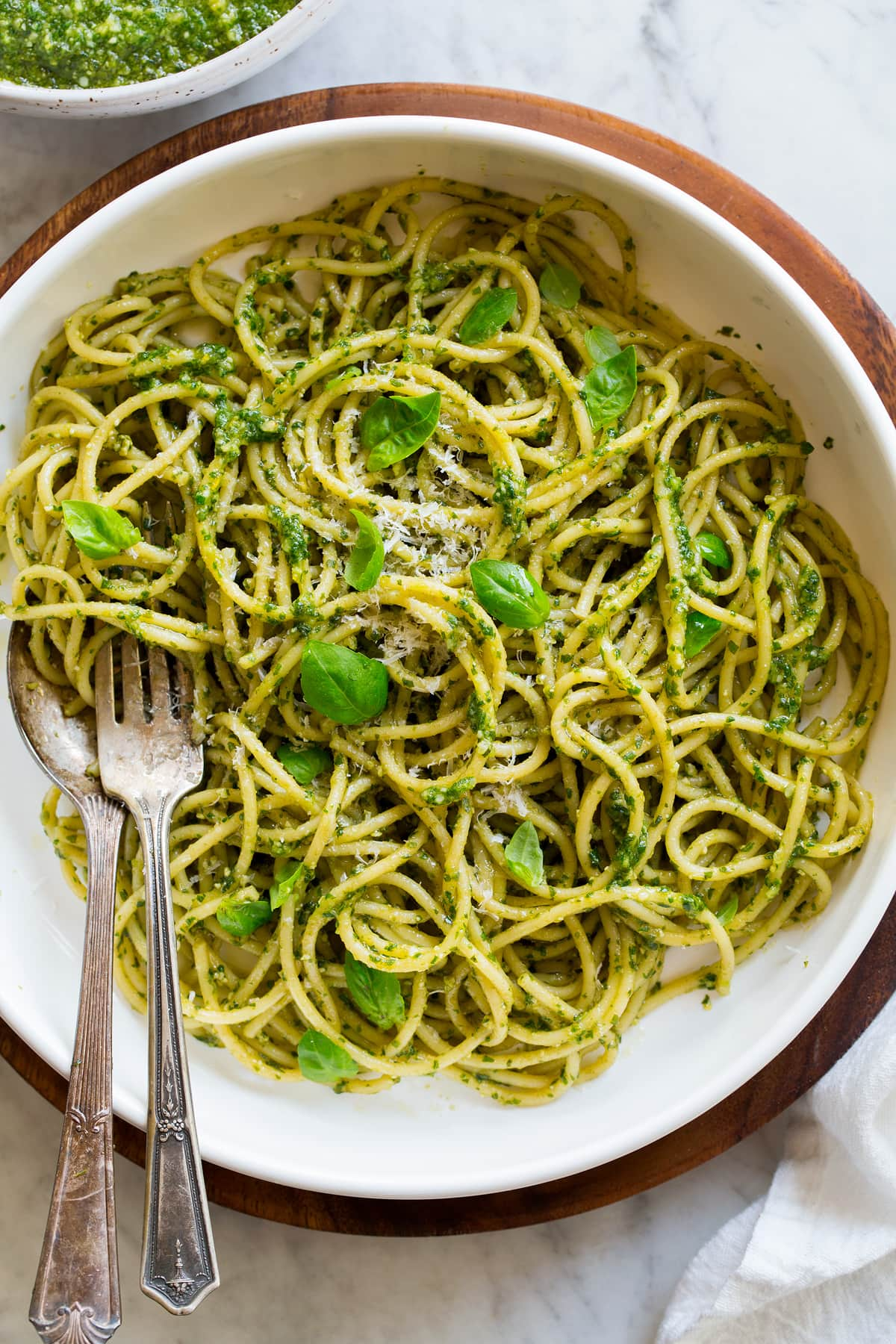 Image showing serving suggestion of pesto. Pesto is tossed of freshly cooked spaghetti pasta in a pasta bowl.