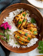 Thai Coconut Grilled Chicken Thighs in a wooden serving bowl with rice and decorative flowers.