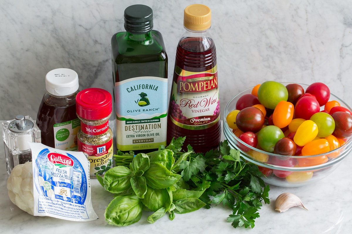 Image of ingredients used to make tomato salad. Includes cherry and grape tomatoes, fresh basil and parsley, garlic, fresh mozzarella, dried oregano, honey, olive oil, red wine vinegar and salt and pepper.