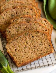 Close up image of sliced zucchini bread on a cutting board with a zucchini and green cloth set to the side.