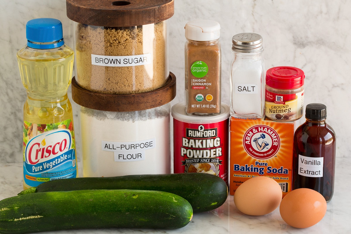 Image of ingredients used to make zucchini bread shown. Includes zucchini, vegetable oil, brown sugar, flour, baking powder, baking soda, salt, eggs, vanilla.
