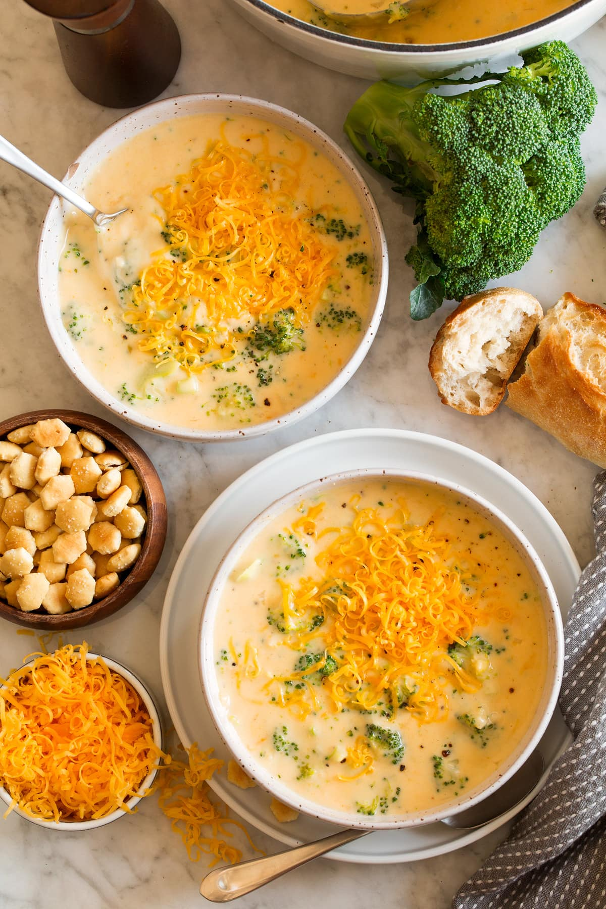 Image overhead of two servings of broccoli cheese soup in serving bowls. Crackers, broccoli, bread and cheese are shown to the side.