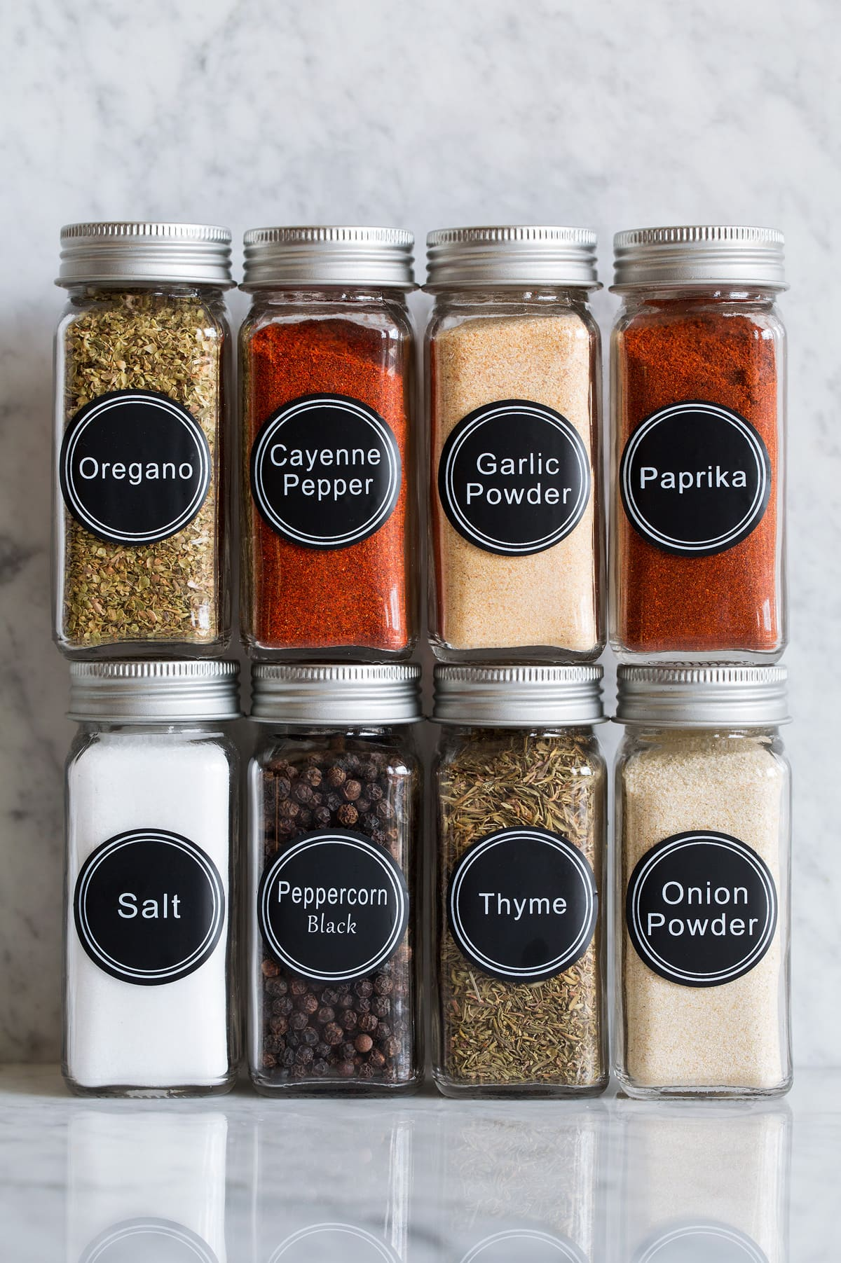 Photo: Eight glass jars of spices that are used to make cajun seasoning shown on a marble surface.