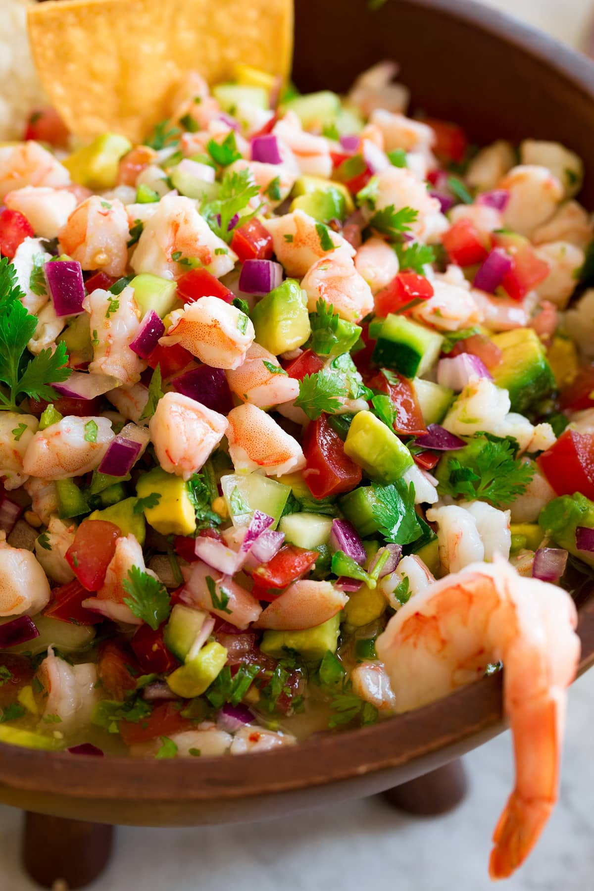 Close up image of shrimp ceviche in a wooden bowl.