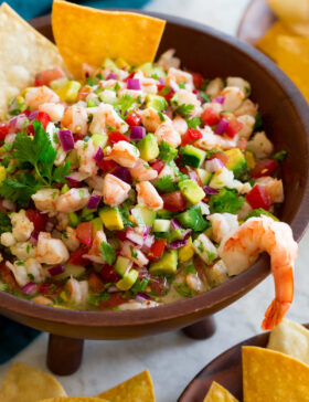 Ceviche in a wooden dip bowl with tortilla chips on the side.
