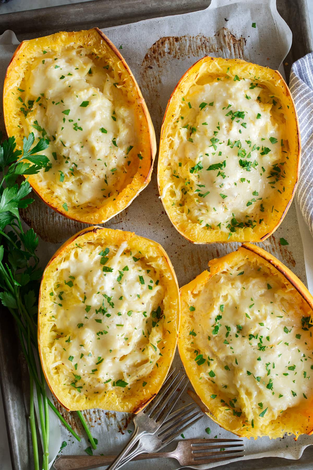 Overhead image of four spaghetti squash filled with cheese, they are resting on a parchment paper lined baking sheet.