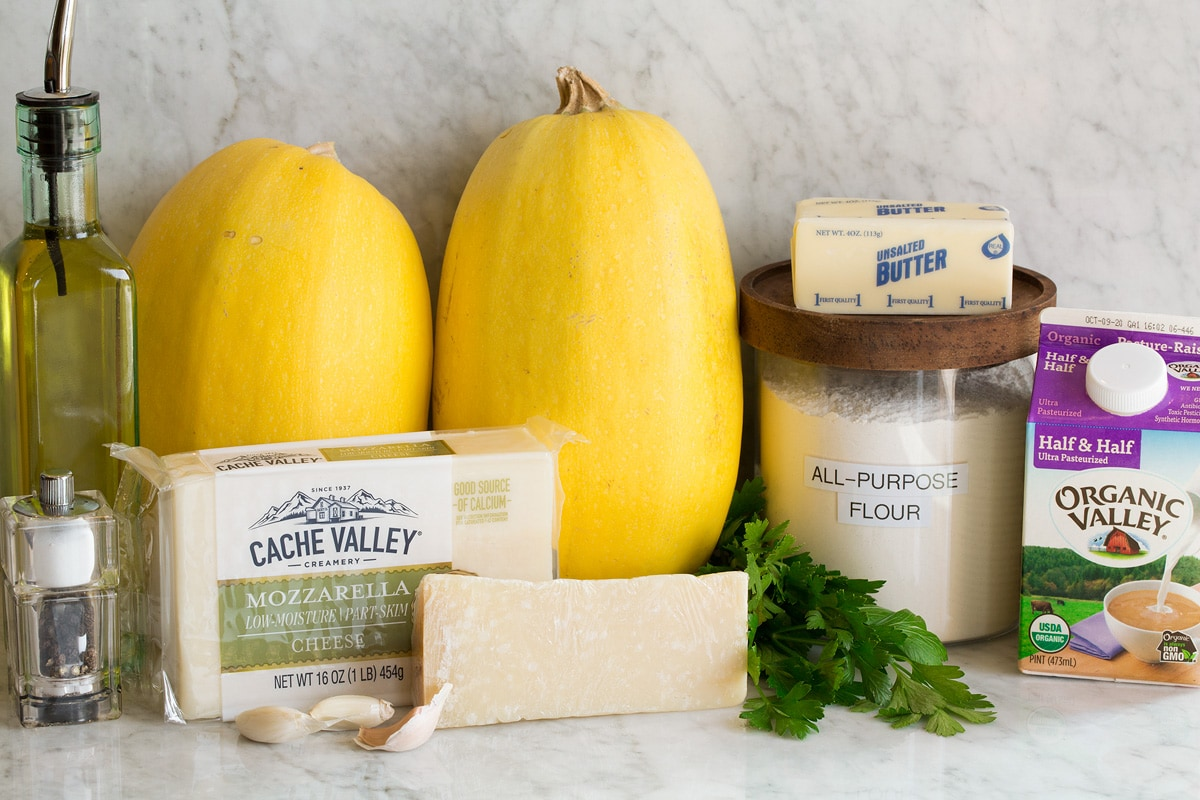 Image of ingredients used to make cheesy spaghetti squash shown. Includes spaghetti squashes, mozzarella, parmesan, half and half, flour, butter, olive oil, garlic, parsley, salt and pepper.