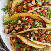 Chicken tacos on a platter shown from a side angle.