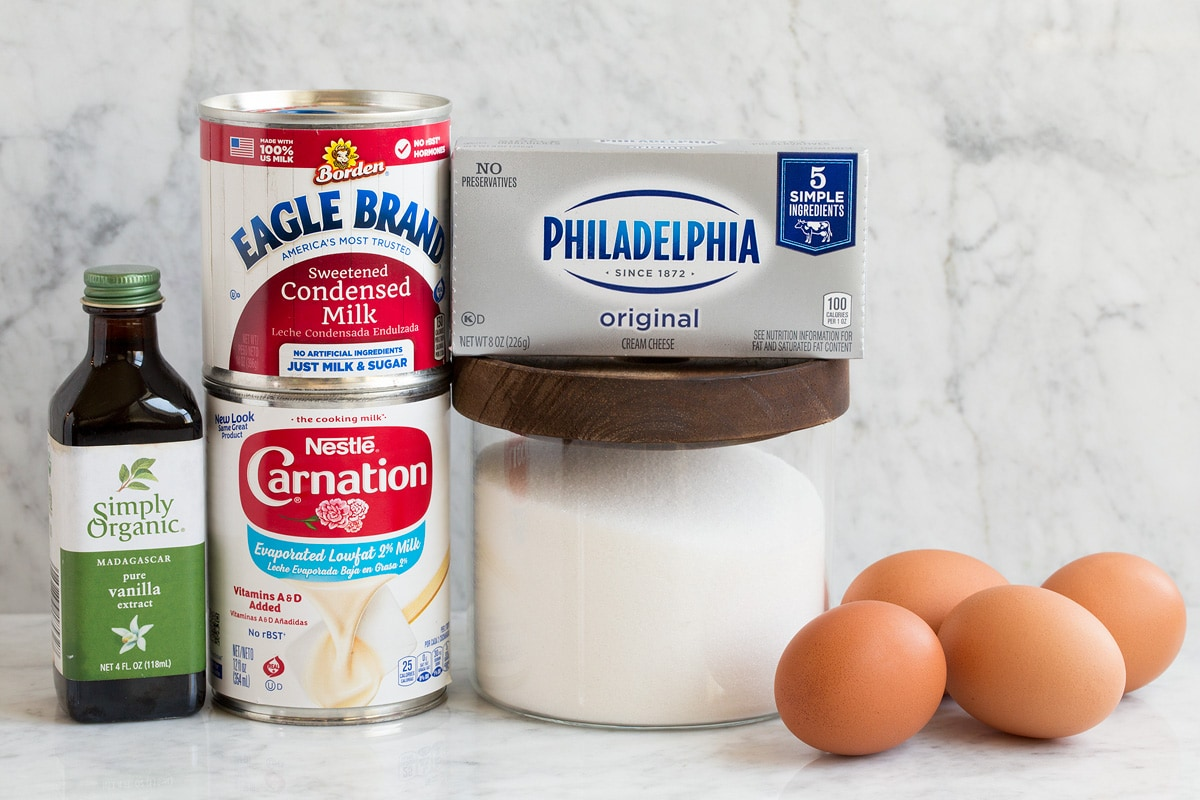 Image of ingredients used to make flan. Shows evaporated milk, sweetened condensed milk, granulated sugar, vanilla, eggs and cream cheese.