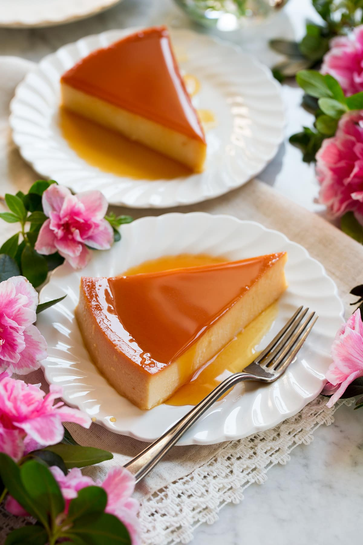 Image of two slices of flan on white scalloped plates with flowers around the sides.
