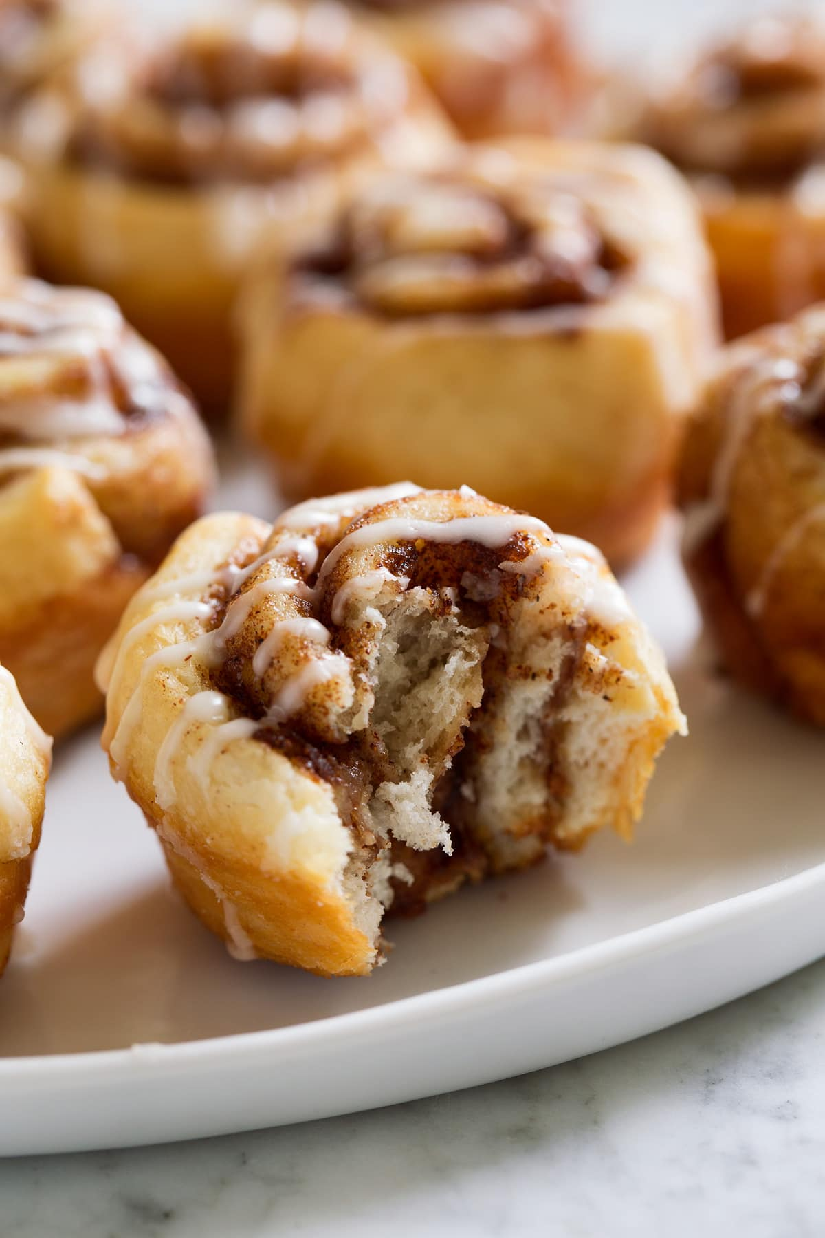 Image of mini cinnamon roll shown bitten into.