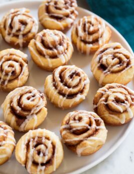Photo of 12 Mini Cinnamon Rolls shown sitting on white platter over a marble surface.