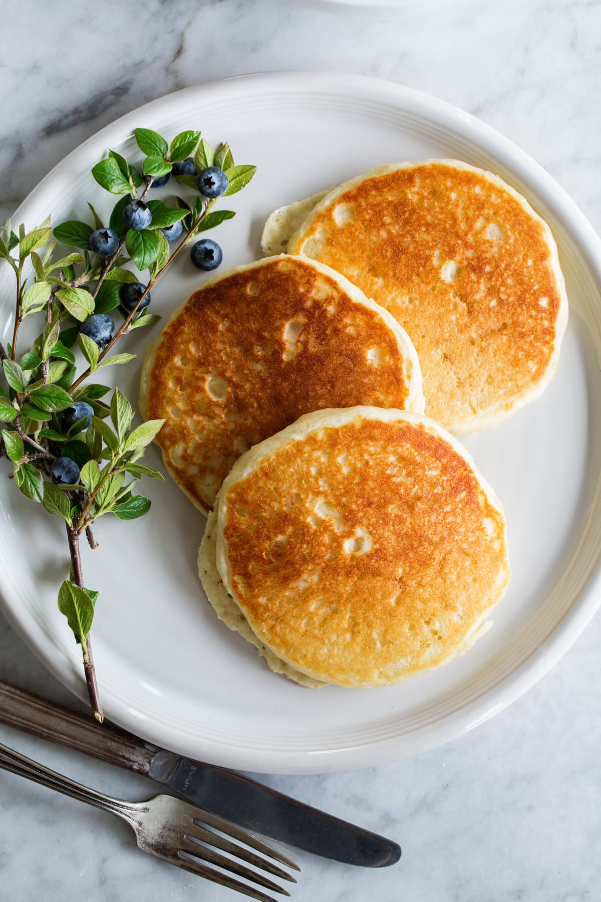 Three pancakes spread out on a large white plate with a blueberry stem to the side.