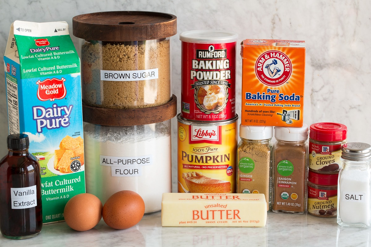 Image of ingredients used to make pumpkin pancakes. Shows flour, brown sugar, salt, baking powder, baking soda, spices, butter, buttermilk, eggs and vanilla.