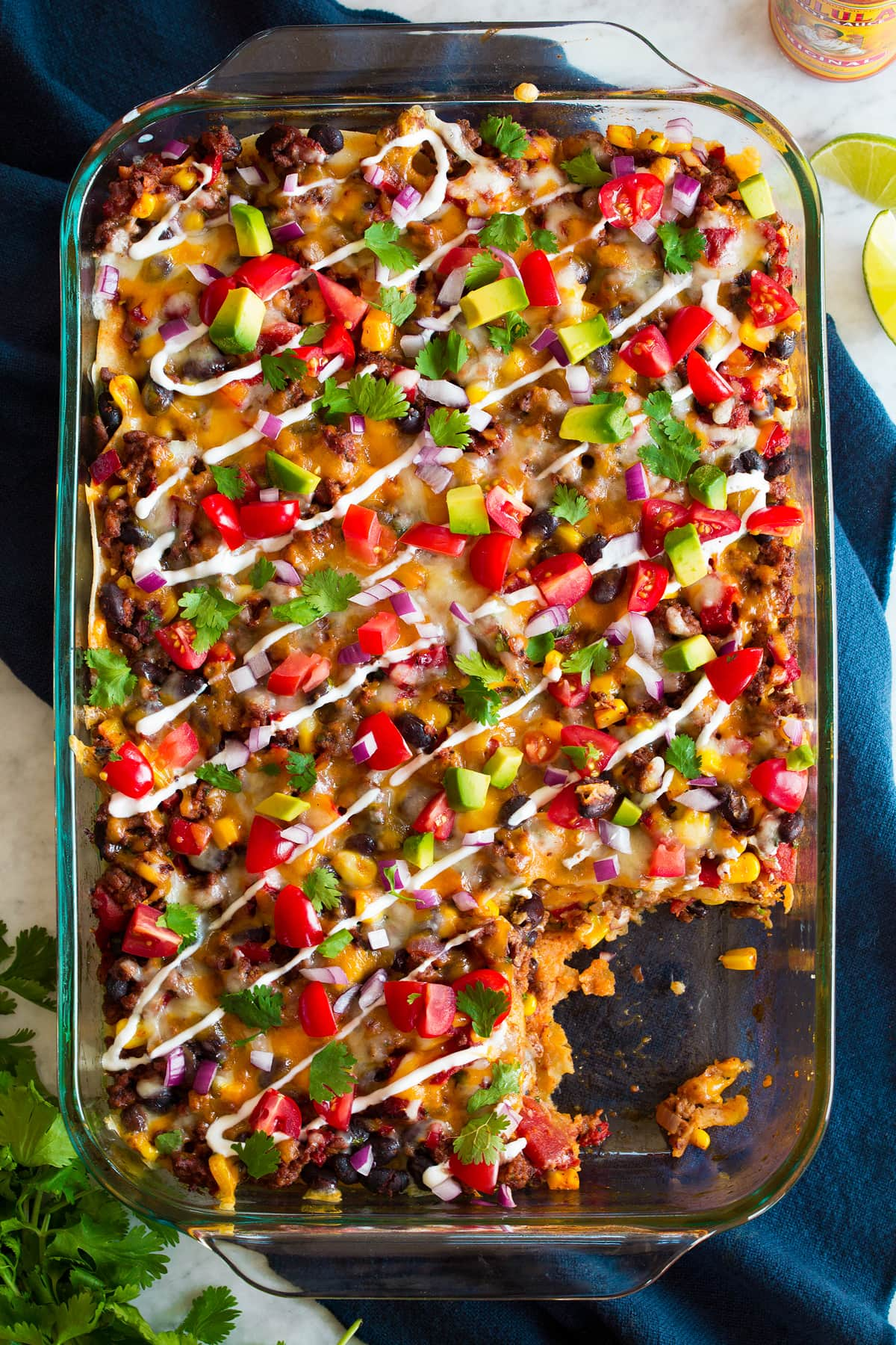 Overhead image of taco casserole in glass baking dish set over a blue cloth.