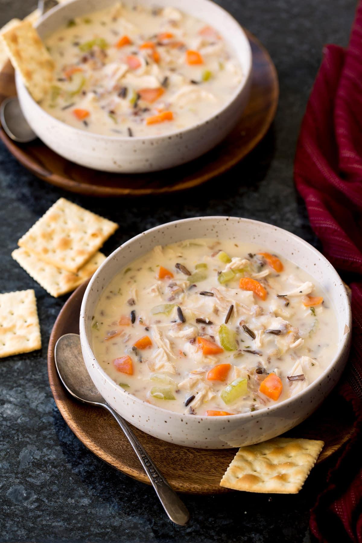 Dos porciones de sopa de pollo y arroz salvaje en platos hondos.