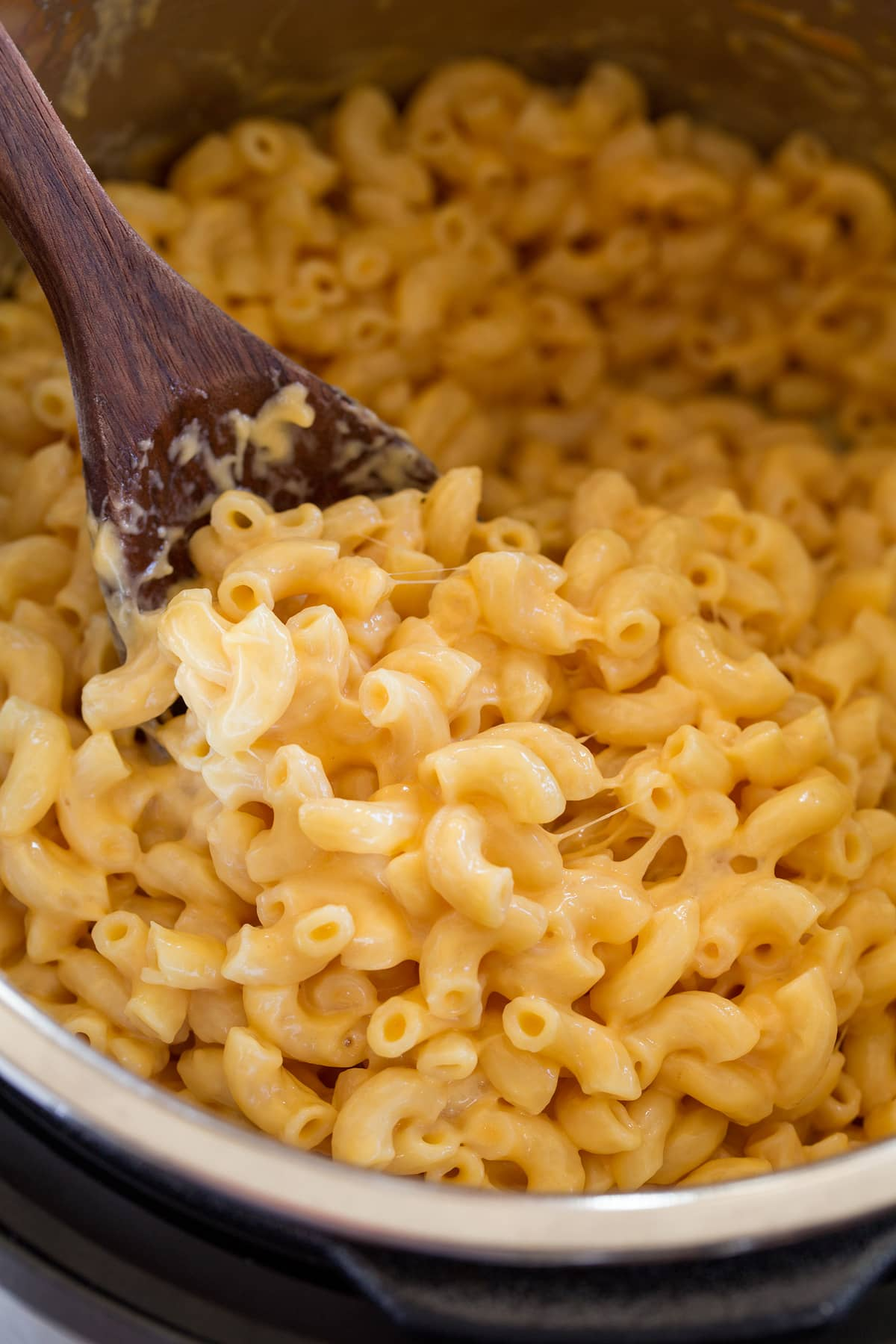 Close up image of mac and cheese being scooped from Instant Pot.