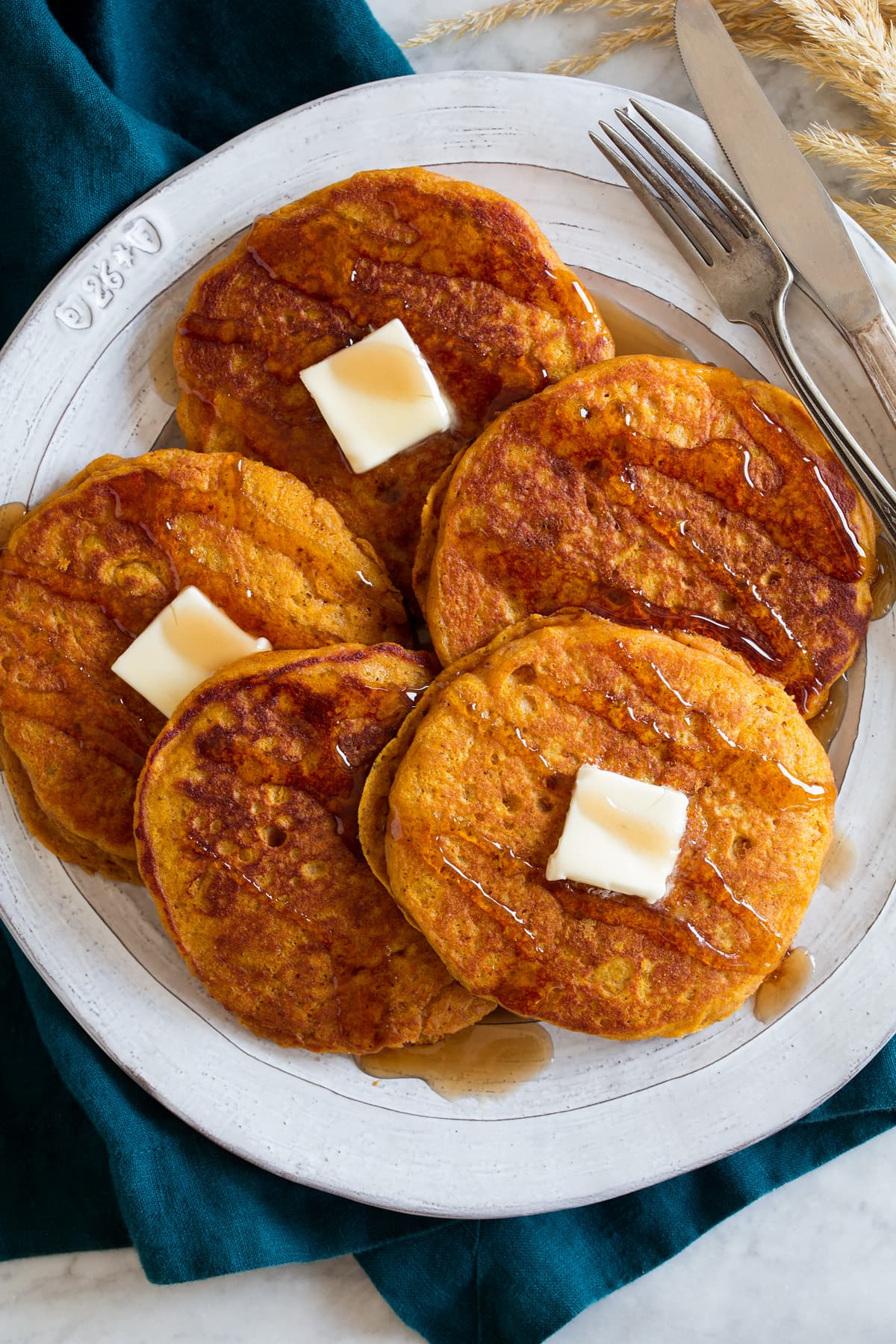 Overhead image of pumpkin pancakes overlapping on a large white plate.