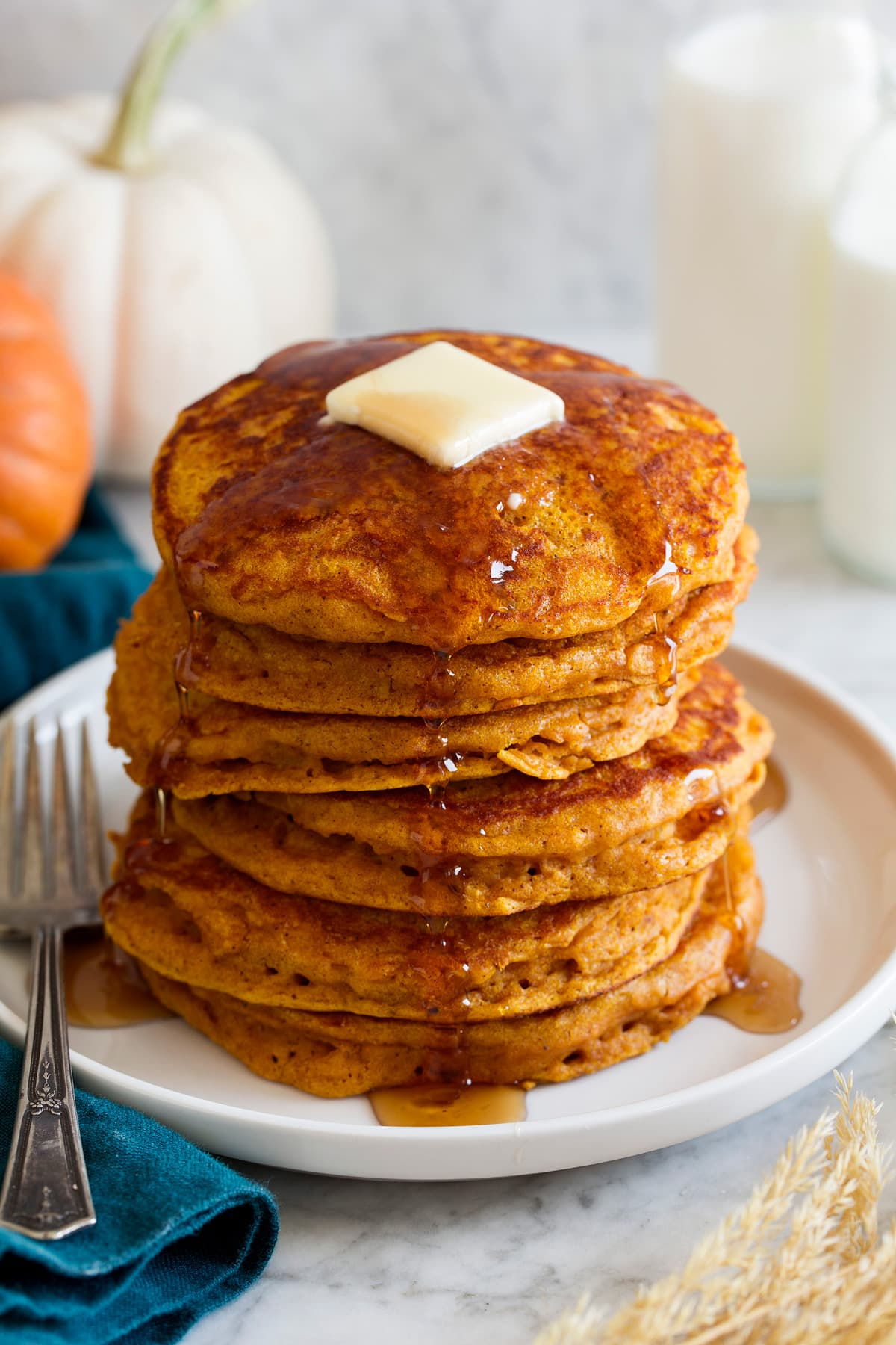 Stack of pumpkin pancakes on a platter. Pancakes are drizzled with maple syrup and topped with butter.