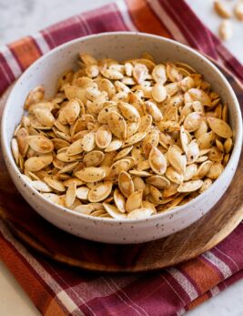 Roasted pumpkin seeds in a bowl set over a red and orange checkered cloth on a marble surface.