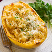 Roasted spaghetti squash half on a white serving plate. Squash it topped with browned butter, parmesan and parsley.