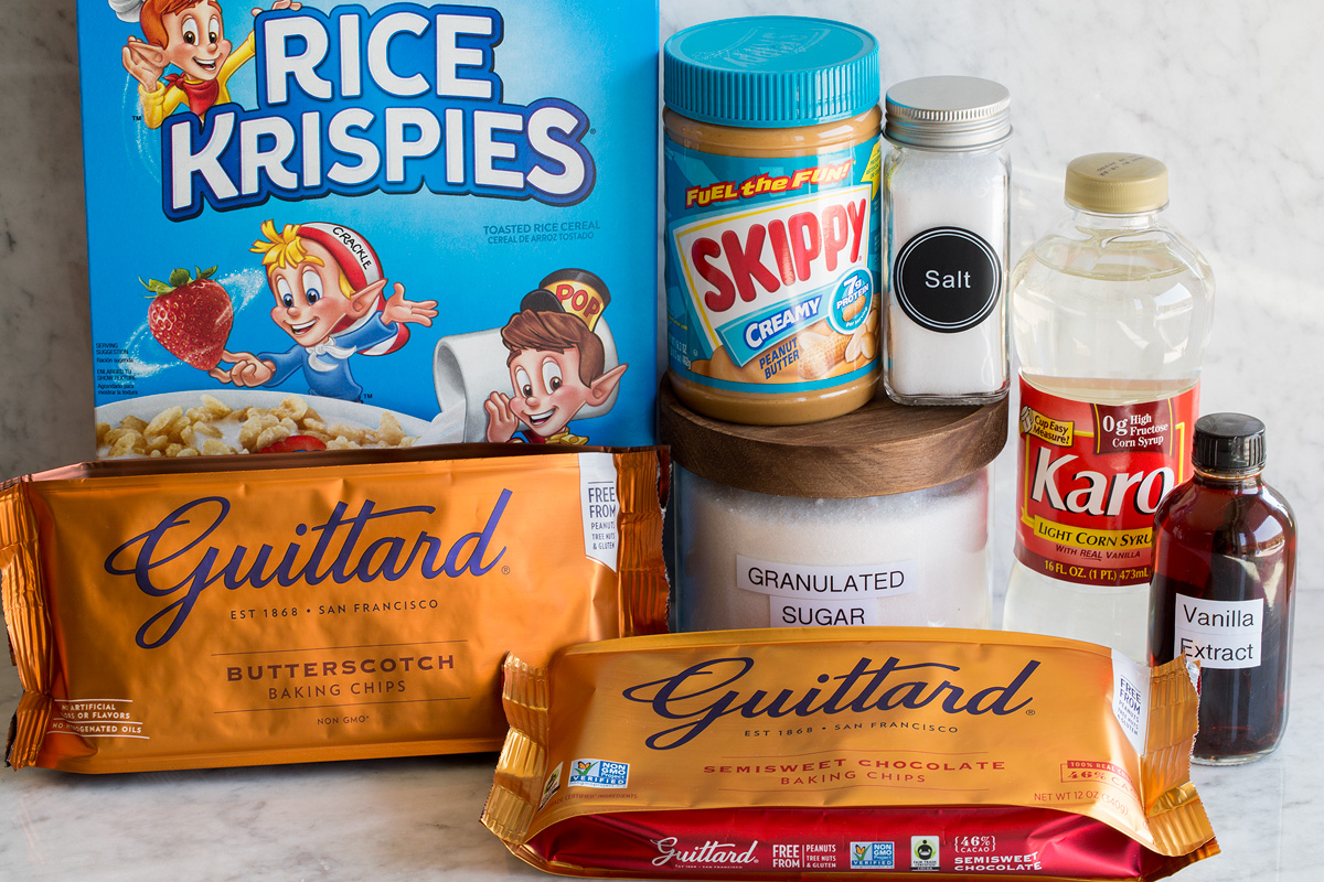 Image of ingredients used to make scotcheroos. Includes rice krispies cereal, peanut butter, sugar, salt, corn syrup, dark chocolate chips and butterscotch chips.