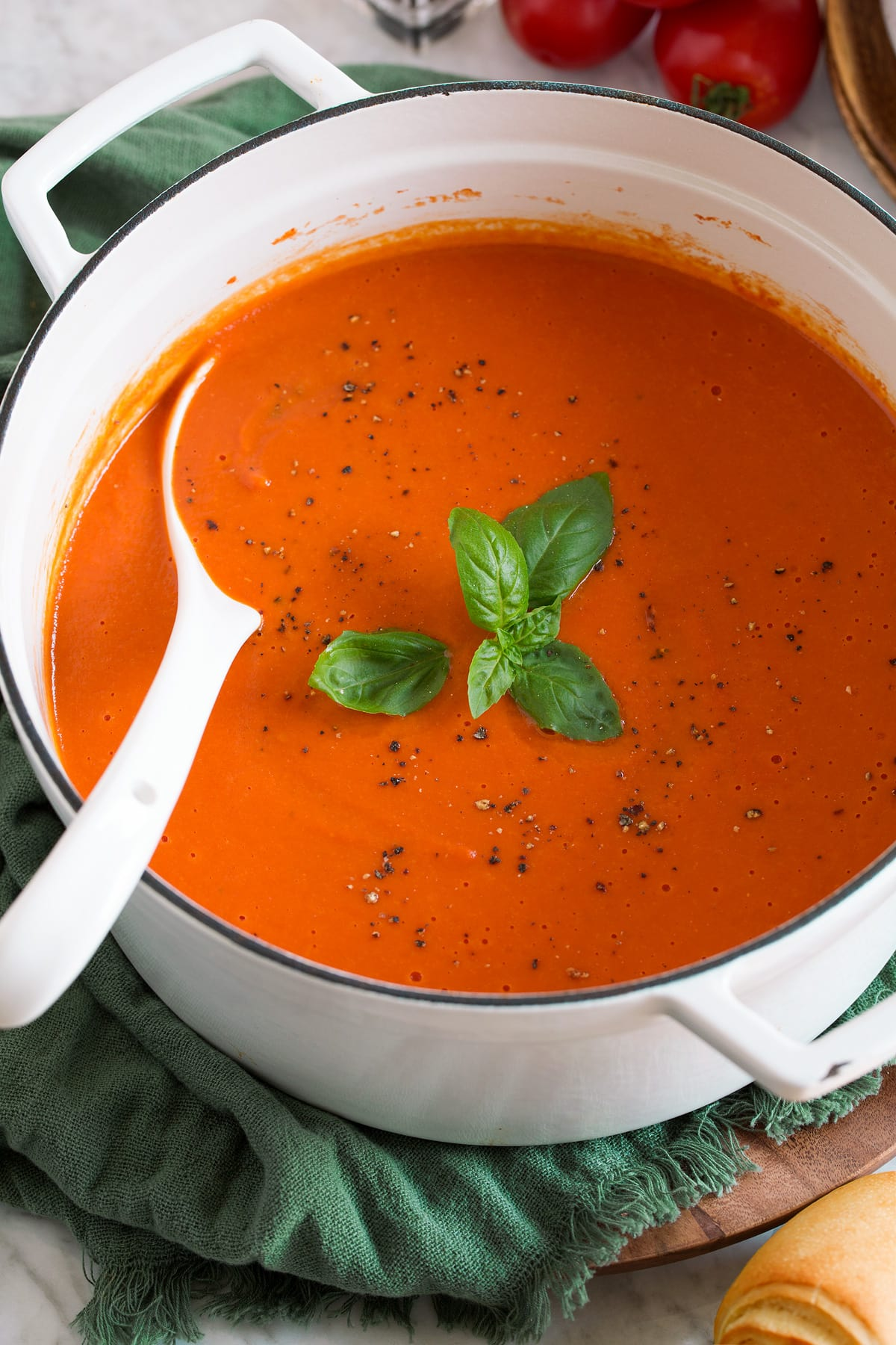 Image of white pot filled with tomato soup that's garnished with basil and pepper.