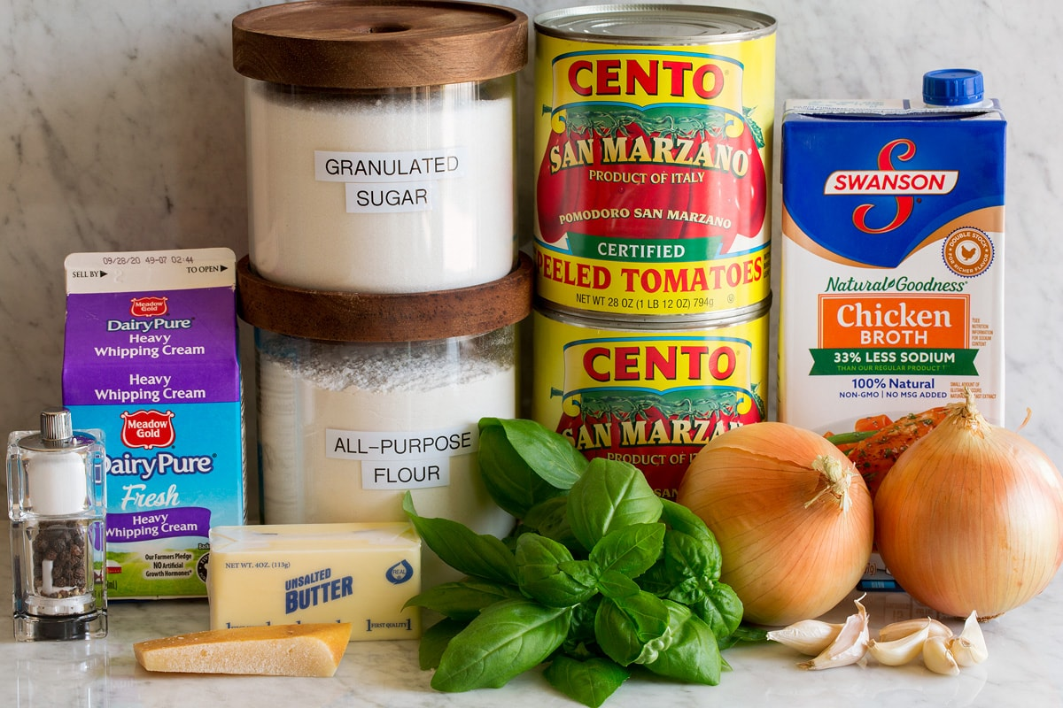Image of ingredients used to make homemade tomato soup. Includes canned san marzano tomatoes, chicken broth, onions, garlic, basil, flour, sugar, butter, parmesan rind, cream, salt and pepper.